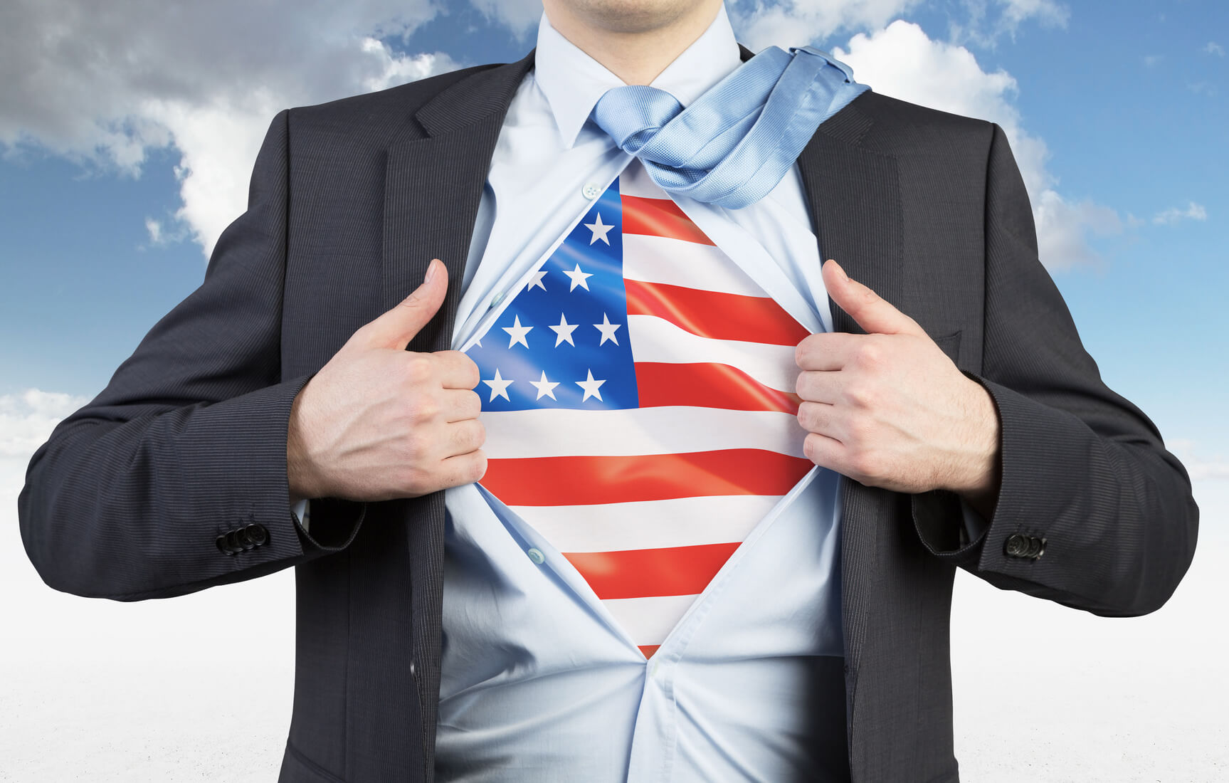 A man tearing the shirt. US flag on the chest. Cloudy sky background.